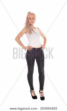 A beautiful blond woman in a white t-shirt and black jeans standing in full body her hands on her hip isolated for white background