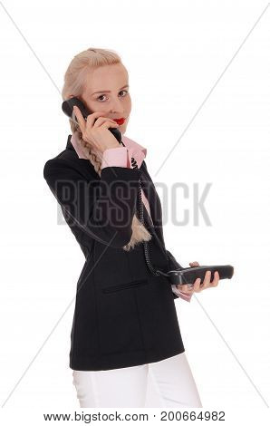 A beautiful business woman in a black jacket and pink blouse standing halve lengths talking on the phone isolated for white background