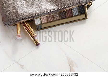 Silver metallic make up bag with eyeshadow palette and gold brushes  spilling out. White marble copy space.