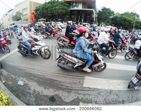 HO CHI MINH CITY, VIETNAM - JULY 25, 2017: Road traffic in Saigon, Vietnam. In the biggest city in Southern Vietnam are more than 4 mil. motorbikes, the traffic is often congested