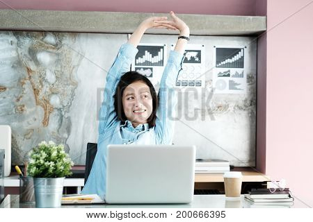 Office woman stretching body for relaxing while working with laptop computer at her desk office lifestyle business situation
