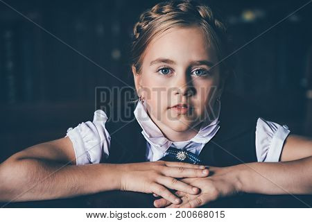 Portrait of a cute girl in elegant classical clothes in the library. Education. Children fashion.