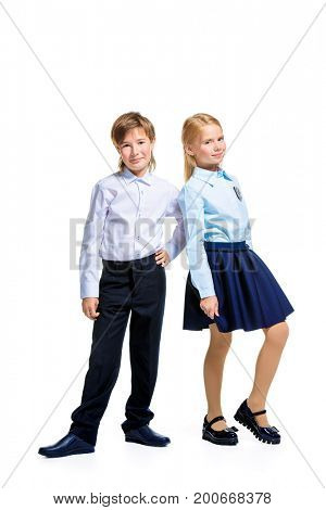 School fashion. Two cute children in school uniform posing at studio. Isolated over white background. Copy space. Full length portrait.