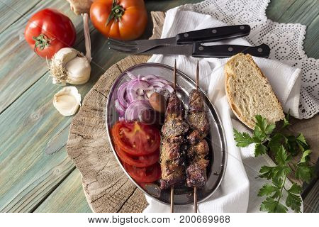 The shashlik and vegetables on a wooden table close-up in a rustic style