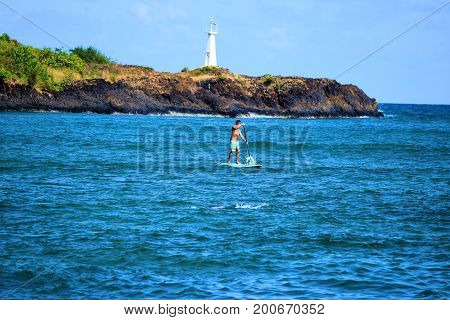 August 1, 2017 at Kalapaki Bay in Kauai, HI:  People surfing and paddle boarding at Kalapaki Bay with Kalapaki Lighthouse beyond where people can swim, surf, and relax on the beach and ocean taken at Lihue in Kauai, HI