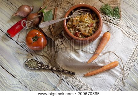 Stewed cabbage in a clay bowl and vegetables on a wooden table close-up