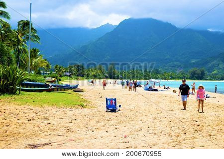 August 1, 2017 at Hanalei Bay in Kauai, HI:  Sandy beach where people are relaxing on the beach surrounded by lush tropical gardens and mountains beyond taken at Hanalei Bay Beach where tourists can sunbathe, swim, and rent boats taken in Kauai, HI