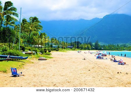 August 1, 2017 in Hanalei Bay at Kauai, HI:  Sandy beach beside lush plants and Palm Trees with mountains beyond taken in Hanalei Bay Beach where people can sunbathe and swim in the ocean taken in Kauai, HI
