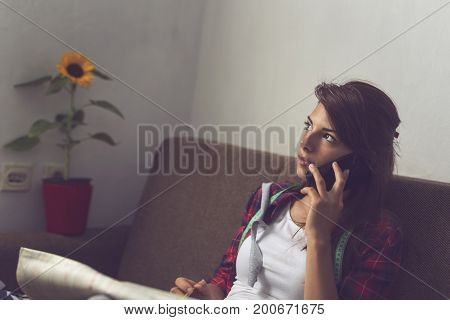 Beautiful young fashion designer sitting on a couch in her atelier making sketches of new dress designs and having a phone conversation