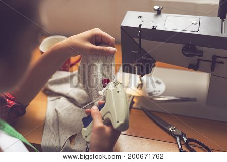 Seamstress attaching a label on a newly made T-shirt with a label gun. Selective focus on the red button