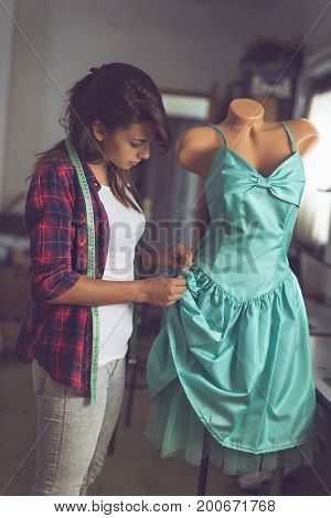 Young fashion designer working on a new dress in her atelier making a fine seams