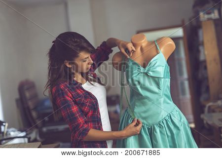 Young fashion designer working on a new dress in her atelier taking measures with measuring tape