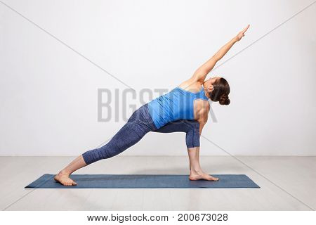 Woman doing Ashtanga Vinyasa yoga asana Parivrtta parsvakonasana - revolved side angle pose on yoga mat on yoga mat in studio on grey bagckground
