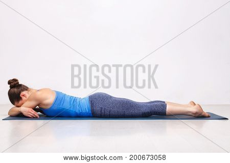 Womand relax in Hatha yoga asana Makarasana - crocodile pose on yoga mat in studio on grey bagckground