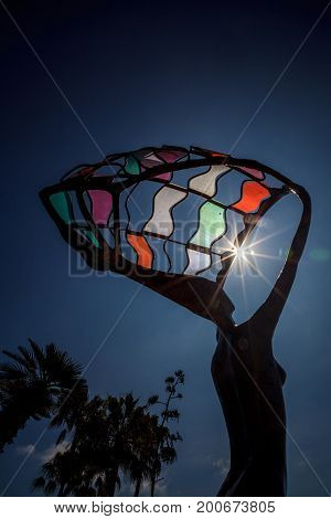 Partial Solar Eclipse Shines Through The Colorful Metal Statue