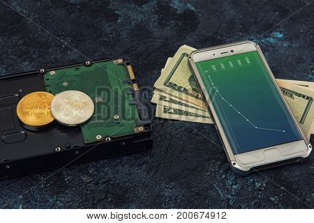 Bitcoin coins with HDD, money and smartphone with diagrams on screen on a dark background