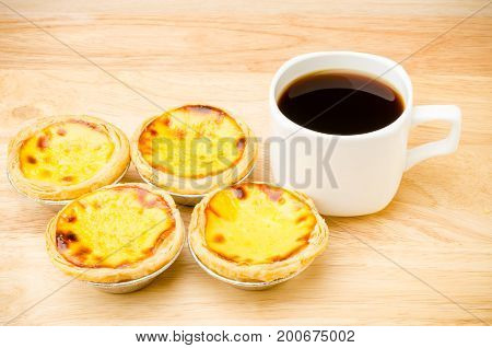 Cup of coffee and egg tart on wooden background,breakfast