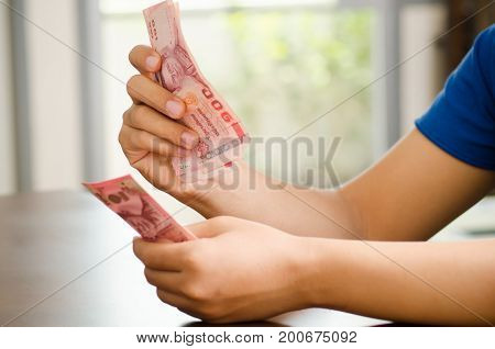 Hand holding 100 Thai baht banknote,Salary or saving money