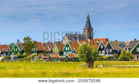 Church towering above Village with colorful wooden houses on the island of Marken in the Ijsselmeer or formerly Zuiderzee the Netherlands