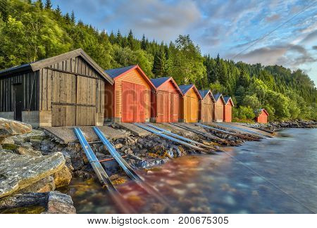 Colorful Boathouse in Norwegian fjord near Rodven in More og Romsdal province Norway at sunset