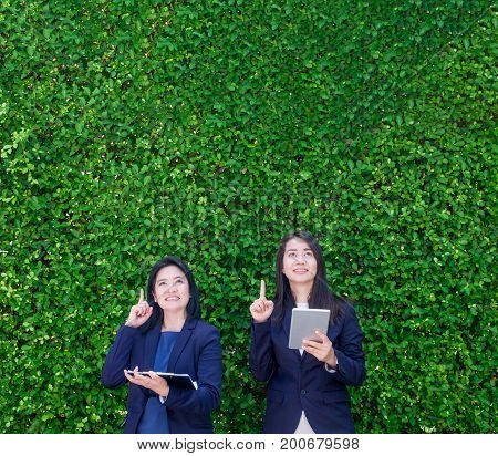 Two Asian businesswoman holding tablet and point finger up to air with thinking action at green leaf wallLeave copy space for adding text or designNew project creating concept