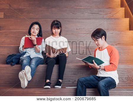 Groups of asian teenage students reading book together at university stair library.
