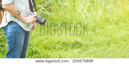 Woman backpacker traveler holding camera standing in patch of green grass in morningTravel wanderlust conceptBanner size leave space for adding text or content for advertise on website.