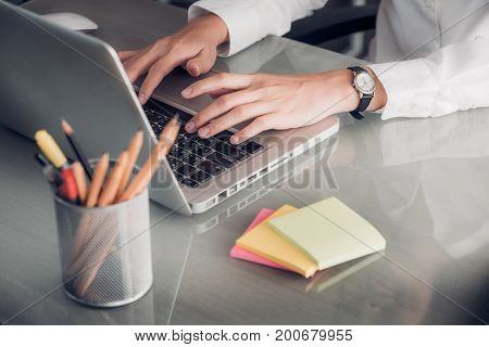 Close up businesswoman hand typing on laptop computer with note paper on office desk.