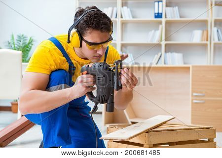 Repairman carpenter cutting sawing a wooden board with an electr