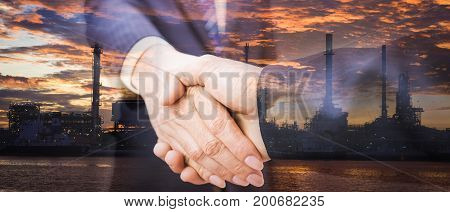 Double exposure of handshake and refinery. handshake on refinery background. refinery on sunrise. Business handshake and business people. Shake hands after their meeting. panoramic banner