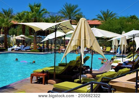 August 9, 2017 in Palm Desert, CA:  Contemporary style furniture including comfortable lounge chairs and umbrellas surrounding a modern pool taken at the Ritz Carlton Resort where guests can swim and sunbathe poolside taken in Palm Desert, CA
