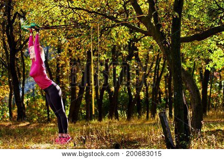 Young woman exercising with suspension trainer in park near autumn trees