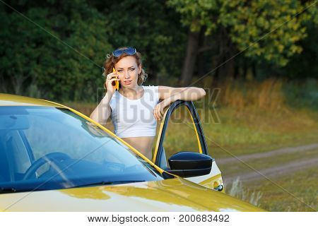 Young attractive girl talking on cell phone. She stands at the open door of the car. Stopover. Call from work.