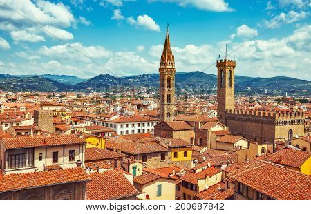Panorama view to tiled roofs and towers of Town hall in Florence old town in Italy. Blue sky with clouds knolls horizon.