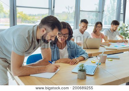 Ready to write. Nice smart positive man holding a pen and leaning on the table while being ready to write