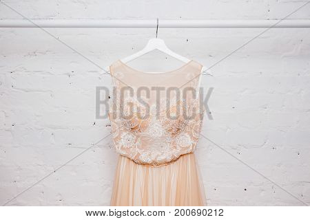 Copy space Wedding dresses for the bride on hangers against a white background of brick in the store. Concept wedding, engagement, attributes, clothing, love.