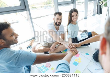 Showing unity. Team of positive enthusiastic people holding hands together and showing their unity while being ready to work