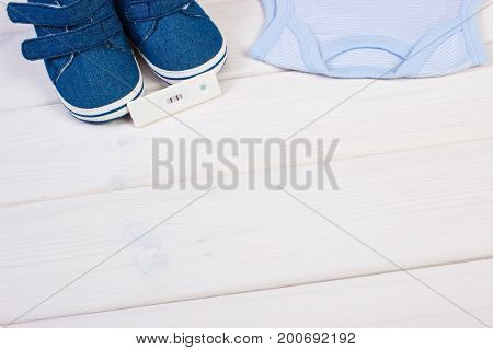 Pregnancy Test With Positive Result And Clothing For Newborn, Expecting For Baby Concept