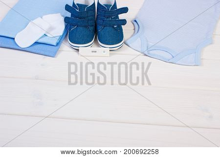Pregnancy Test With Positive Result And Clothing For Newborn And Baby