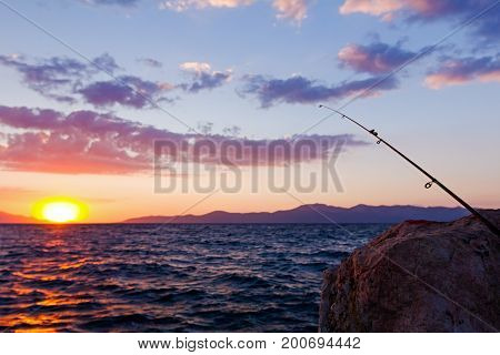 Fishing pole on a rocky beach dock at purple sunset.