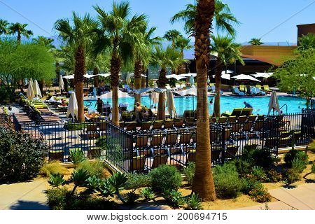August 9, 2017 in Palm Desert, CA:  Comfortable lounge chairs and umbrellas surrounding a contemporary style pool beside Palm Trees and desert cacti gardens taken at the Ritz Carlton Resort where guests can swim and sunbathe poolside taken in Palm Desert,