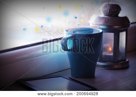 Winter decoration with lantern, hot tea cup, e-book reader and lights on window .