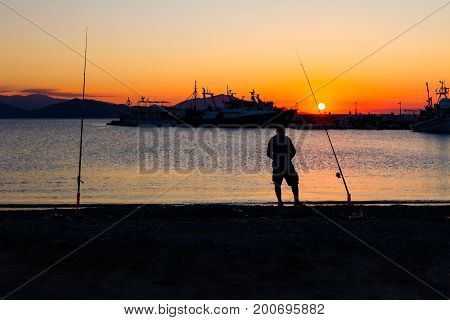 Silhouette of a senior man is fishing from the beach in background dock at sunset.