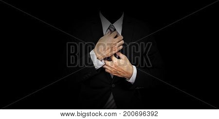 Businessman in black suit on panoramic black background
