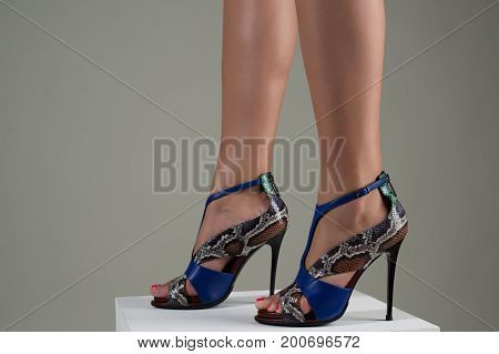 Beautiful female feet in stylish blue high-heeled sandals.