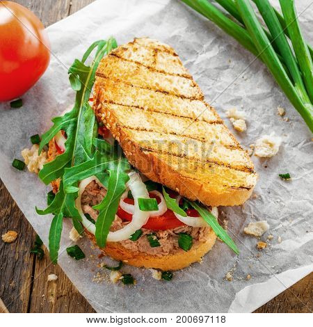 Fish sandwich made of grilled toast tuna salad and vegetables on a rustic wooden table. Delicious healthy diet meal. Top view.