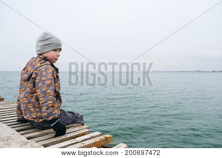 The child sits on the pier and watching the sea in winter.