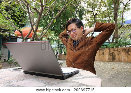 Portrait of tired young businessman stretch oneself on outdoor background