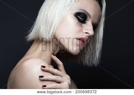 Beautiful blond girl with dark smokey makeup and art manicure design nails. beauty face. Photos shot in studio
