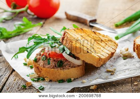 Classic tuna salad sandwich with tomato onion and arugula on a table. Delicious healthy meal made of fish vegetables and toasts.
